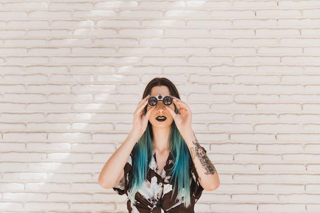 Mujer joven que mira a través de la situación binocular delante de la pared