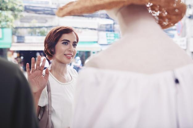 Mujer joven que mira un vestido hermoso