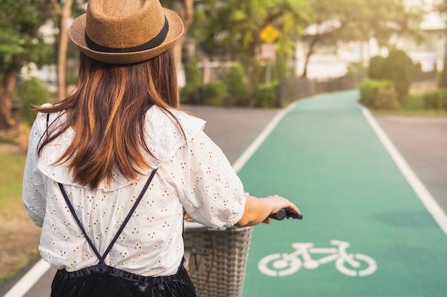 Mujer joven que monta en bicicleta en el carril bici en el parque