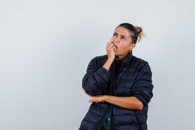 Mujer joven que muerde el puño mientras mira hacia arriba en chaqueta acolchada y mirando pensativo. vista frontal.