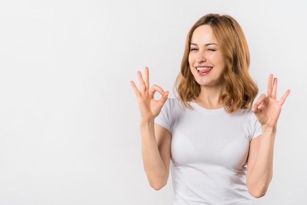 Mujer joven que muerde su lengua que muestra gesto aceptable con dos manos que guiñan un ojo