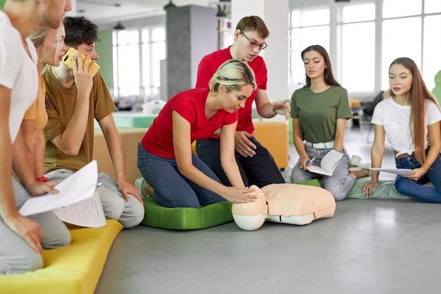 Mujer joven que muestra cómo salvar la vida en la clase de rcp