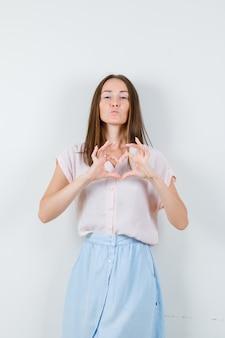 Mujer joven que muestra el gesto del corazón con los labios doblados en camiseta, falda, vista frontal.