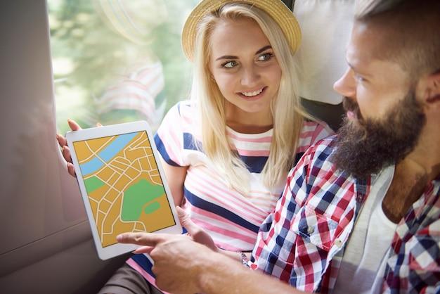 Mujer joven que muestra el mapa de la ciudad para hacer turismo