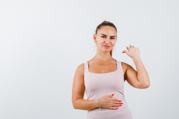 Mujer joven que muestra la palma en camiseta y parece confiada. vista frontal.
