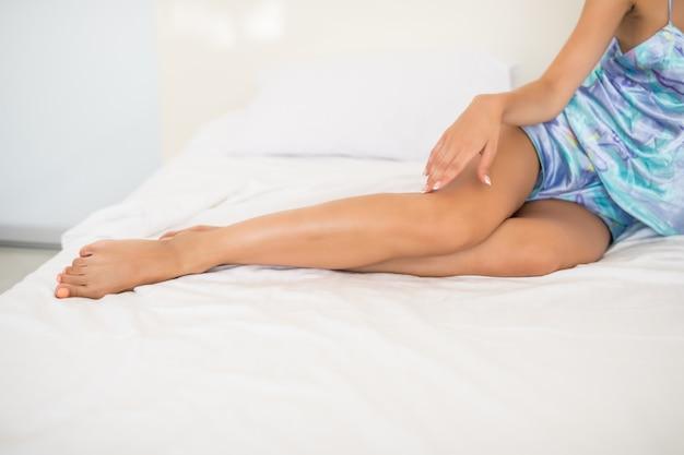 Mujer joven que muestra las piernas lisas de piel sedosa después de la depilación en la cama en su casa