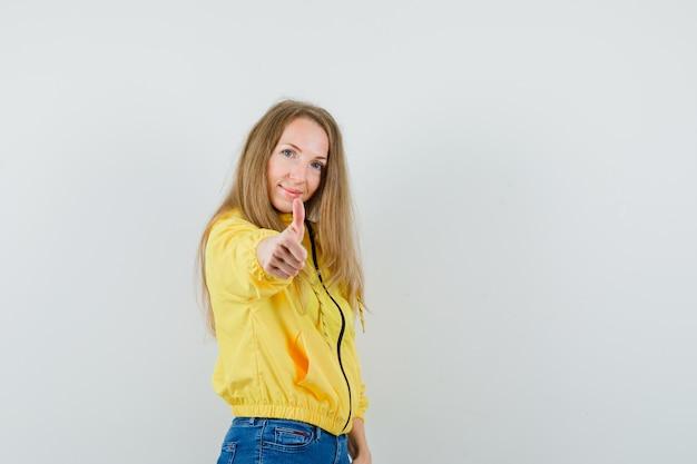 Mujer joven que muestra el pulgar hacia arriba en chaqueta de bombardero amarilla y jean azul y parece optimista. vista frontal.