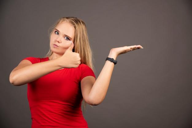 Mujer joven que muestra el pulgar hacia arriba en la pared negra.