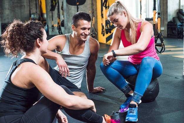 Mujer joven que muestra el reloj de pulsera a sus amigos en el gimnasio