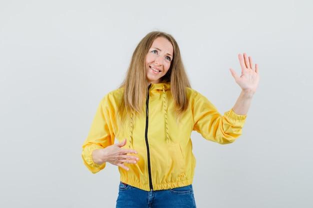 Mujer joven que muestra la señal de stop y que sonríe en chaqueta de bombardero amarilla y jean azul y parece optimista. vista frontal.