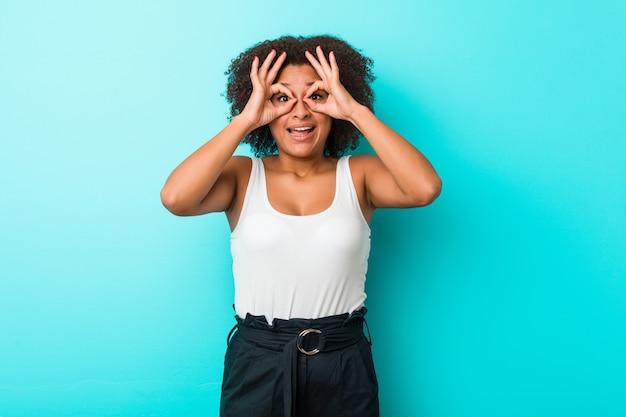 Mujer joven que muestra signo bien sobre los ojos