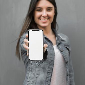 Mujer joven que muestra smartphone en la mano