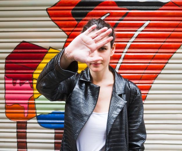 Mujer joven que oculta su cara con la mano