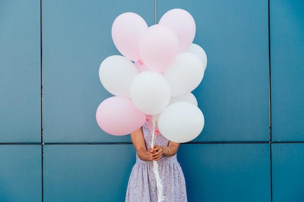 Mujer joven que oculta su cara con el manojo de globos, colocándose contra la pared azul.