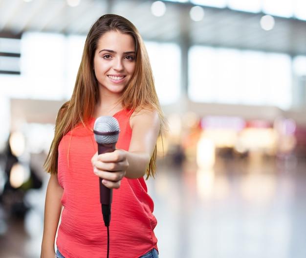 Mujer joven que ofrece un micrófono en el fondo blanco