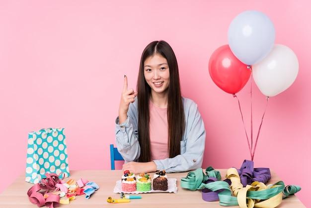 Mujer joven que organiza un cumpleaños aislado mostrando el número uno con el dedo
