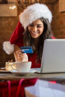Mujer joven que paga su cuenta en un café con sombrero de navidad