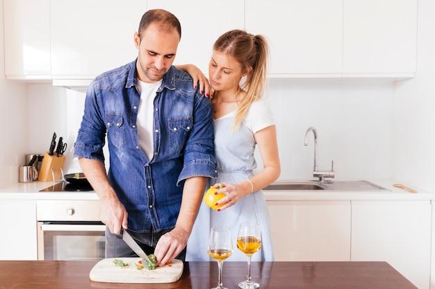 Mujer joven que está parada detrás del hombre que corta el bellpepper con el cuchillo en la tabla