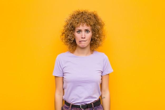Mujer joven que parece confundida y confundida, mordiéndose el labio con un gesto nervioso, sin saber la respuesta al problema sobre la pared naranja