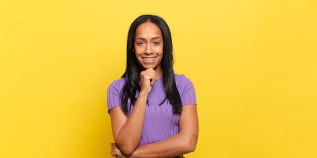 Mujer joven que parece feliz y sonriente con la mano en la barbilla, preguntándose o haciendo una pregunta, comparando opciones