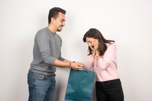 Mujer joven que parece feliz por su regalo de su novio.