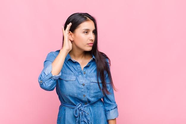 Mujer joven que parece seria y curiosa, escuchando, tratando de escuchar una conversación secreta o chismes, escuchando a escondidas
