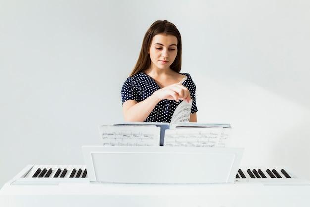 Mujer joven que pasa las páginas de la hoja musical contra la pared blanca.