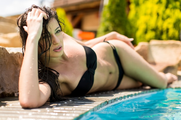 Mujer joven que pone por la piscina