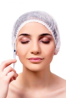 Mujer joven que se prepara para la cirugía plástica aislada en blanco