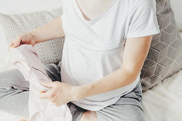 Mujer joven que prepara la ropa para el bebé