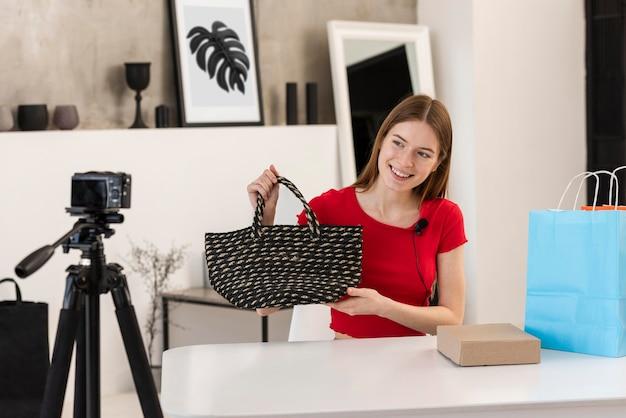 Mujer joven que presenta el bolso comprado en cámara