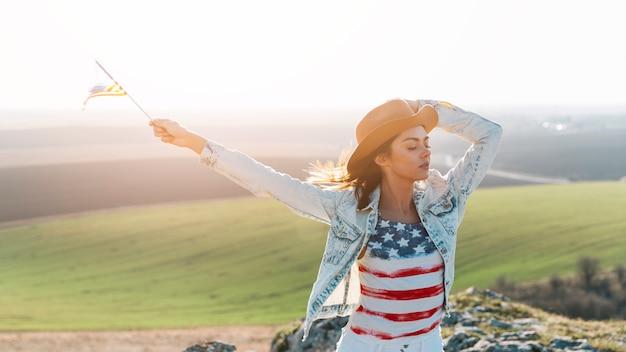 Mujer joven que presenta en camiseta de la bandera americana encima de la montaña