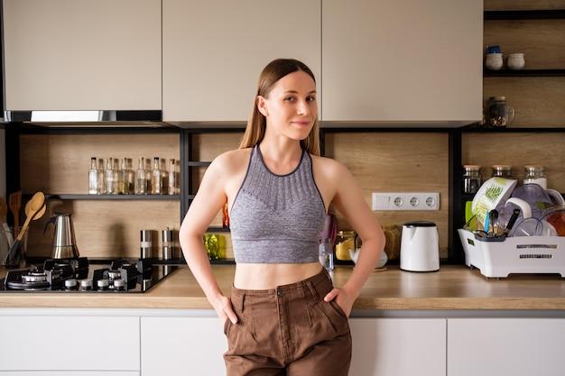 Mujer joven que presenta en fondo moderno de la cocina