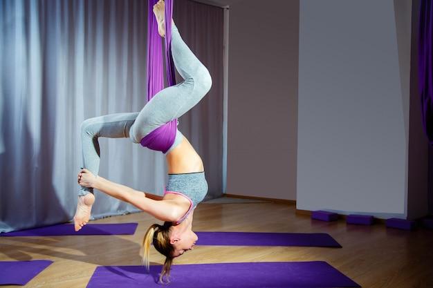 Mujer joven que presenta haciendo ejercicio aéreo de la yoga con la hamaca al revés.