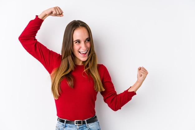 Mujer joven que presenta levantando el puño después de una victoria, concepto ganador.