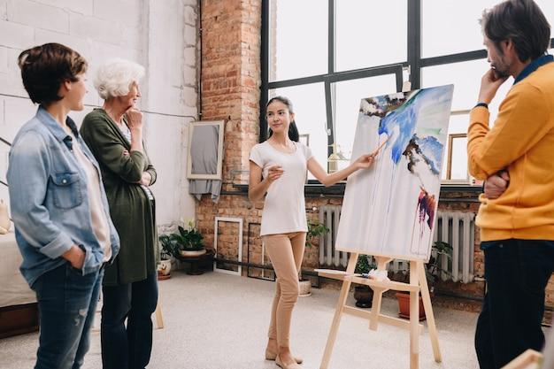 Mujer joven que presenta pintura en art studio