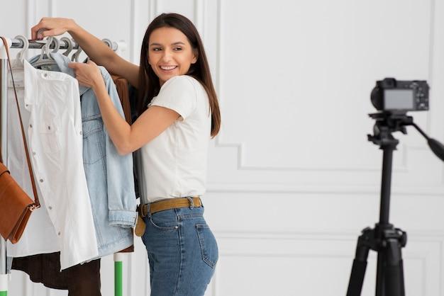 Mujer joven que presenta ropa nueva