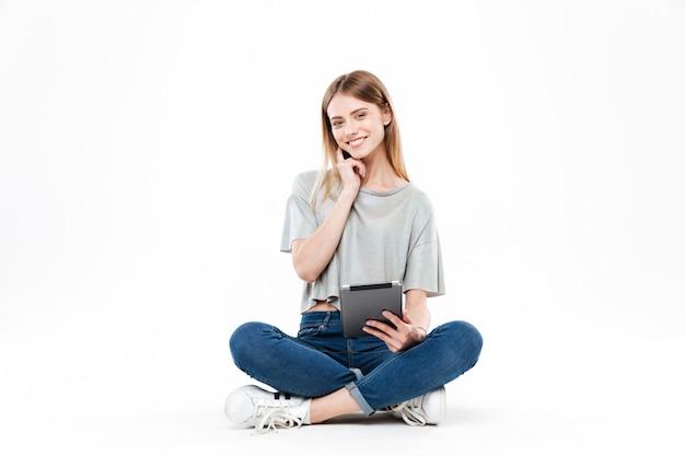 Mujer joven que presenta con la tableta aislada