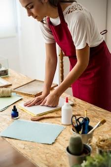 Mujer joven que presiona la pulpa de papel en molde