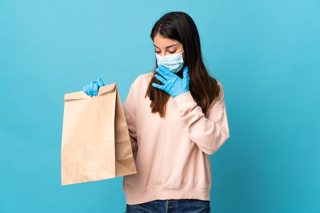 Mujer joven que se protege del coronavirus con una máscara y sostiene una bolsa de la compra aislada en azul con sorpresa y expresión facial conmocionada.