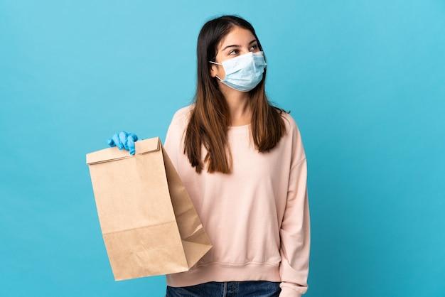 Mujer joven que se protege del coronavirus con una máscara y sostiene una bolsa de compras aislada en azul mirando hacia arriba mientras sonríe