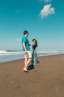 Mujer joven que quiere que su hombre siga a la línea de costa en la playa