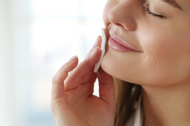 Mujer joven que quita maquillaje facial con toallitas desmaquillantes.