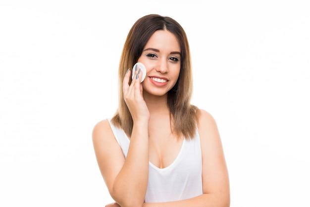 Mujer joven que quita maquillaje de su cara con el cojín de algodón