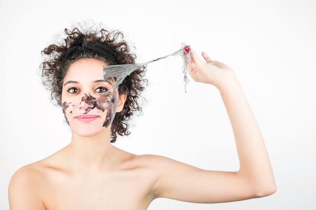 Una mujer joven que quita la máscara del carbón de leña aislada contra el contexto blanco
