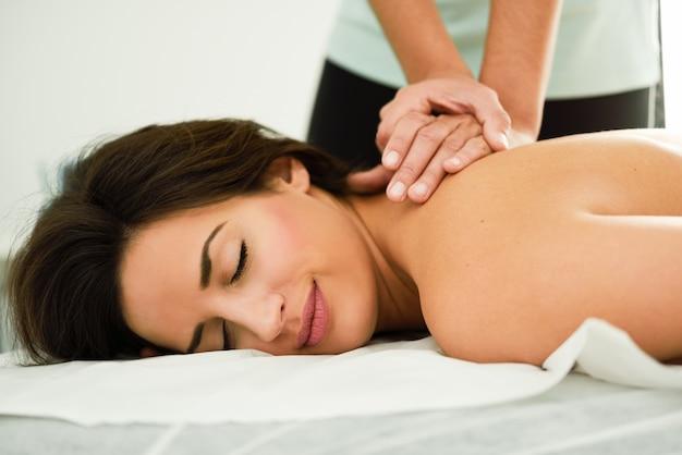 Mujer joven que recibe un masaje de espalda en un centro de spa.