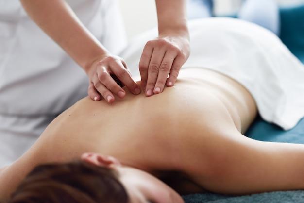 Mujer joven que recibe un masaje de espalda por un terapeuta profesional.
