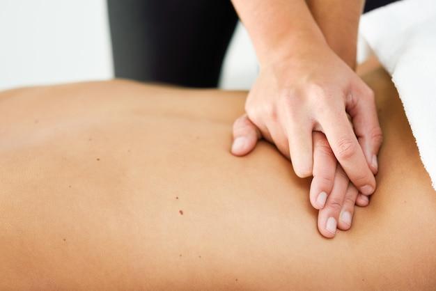 Mujer joven que recibe un relajante masaje de espalda en un centro de spa.