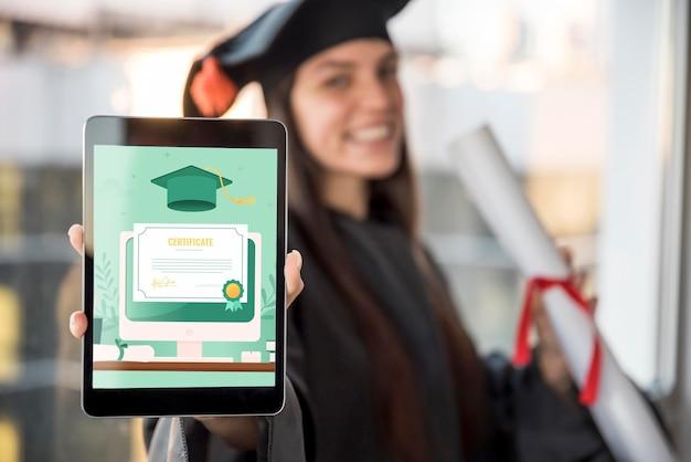 Mujer joven que recibe su diploma en una tableta
