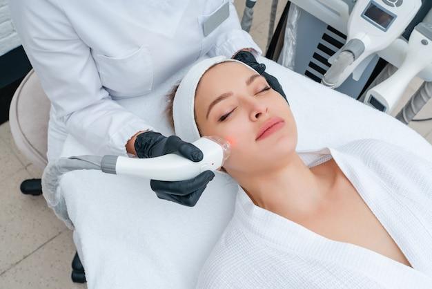 Mujer joven que recibe tratamiento con láser en la clínica de cosmetología